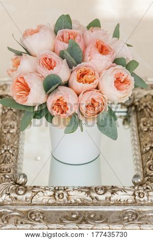 Wedding decorating bouquet of pink roses and green petals, in vhite vase, standing on mirror