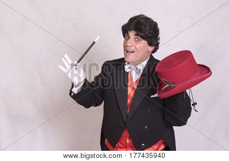Mature magician with a red hat and a wand, taken on a white background