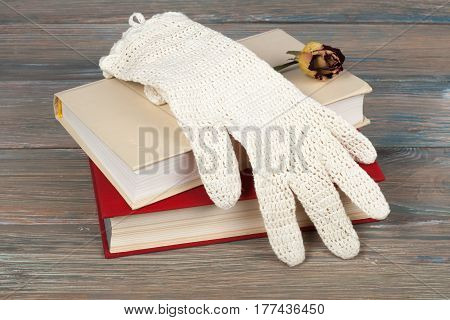 Book stacking. Open book hardback books on wooden table background. Back to school. Copy space for text. Knitted gloves