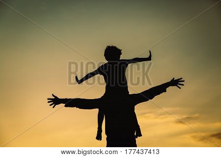 happy father and little son play on sunset sky