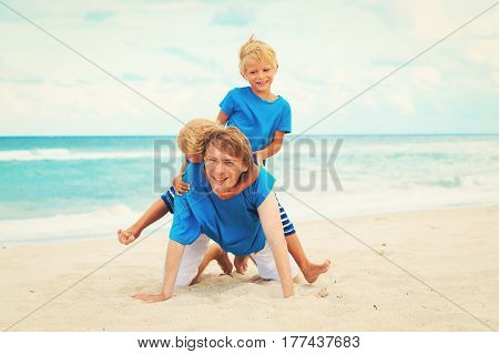 happy father with little son and daughter play on beach