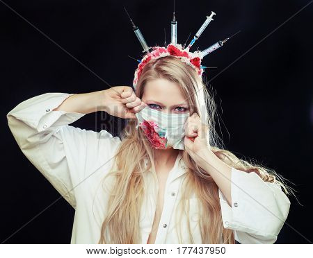 Halloween costume of a crazy nurse with crown made of syringes and a syringe in the hand