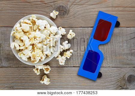 Popcorn and 3d anaglyph glasses on wooden table top view