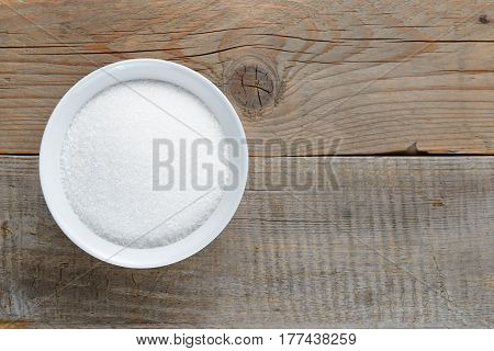 White sugar in bowl on wooden table top view