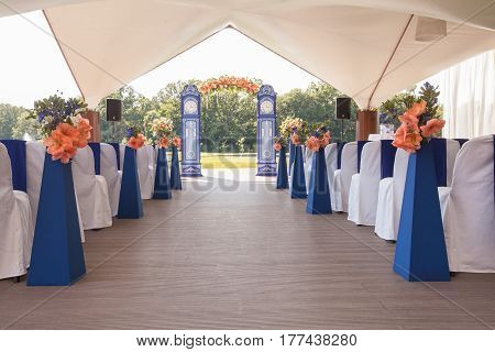 Beautiful wedding archway. Arch like blue clocks decorated with peachy flowers, indoor, pavilion