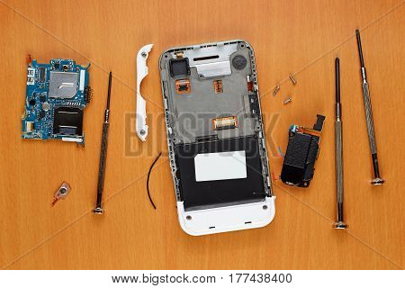 Broken smartphone and screwdrivers on table top view
