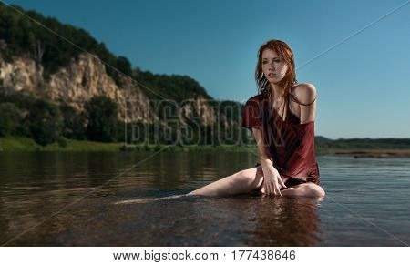 Yung beautiful redhead girl in wet burgundy shirt sitting in the river on a background of blue sky and mountains in the summer