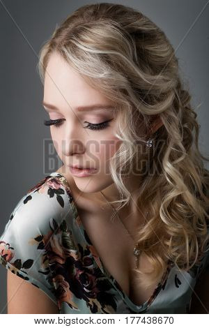 portrait of a beautiful young girl blonde with downcast eyes in the flowery dress