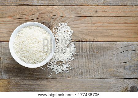 Jasmine rice in bowl on wooden table top view