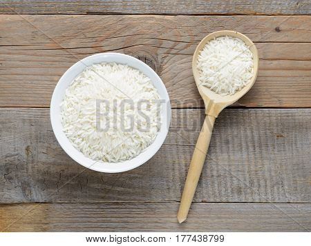 Jasmine rice in bowl and spoon on wooden table