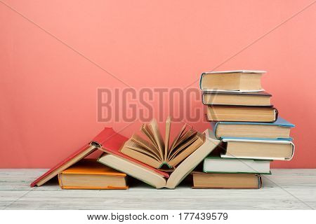Book stacking. Open book hardback books on wooden table and pink background. Back to school. Copy space for text.