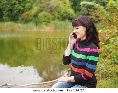 Beautiful Young Woman Talking On Smart Phone At Autumn Park. Pretty Young Woman In Autumn Clothes Se