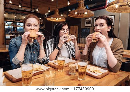 Unhealthy food. Attractive brunette wearing glasses looking enigmatically at her neighbor while eating tasty meal