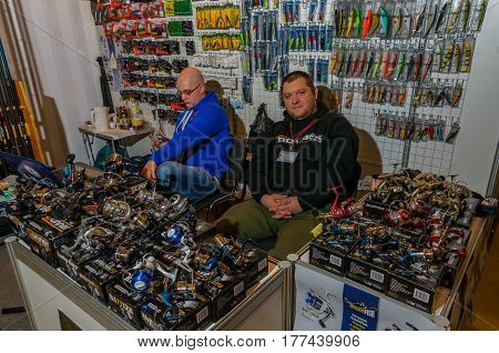 Moscow Russia - February 25 2017: Two sellers of fishing gear waiting for customers behind the counter with spinning reels