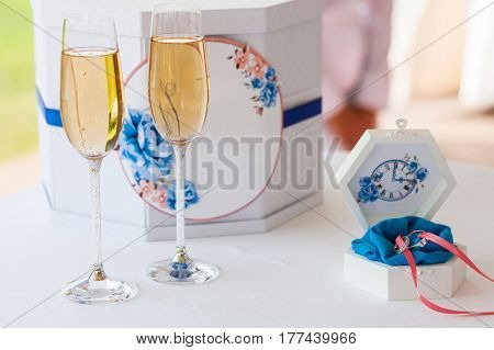 Wedding decorated mail box for greeting letters and tender white casket with coulomb on small round table, with two glasses with champagne