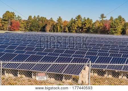 Solar panels in a field with high voltage sign