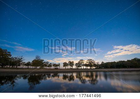 Cielo stellato azurro con gli alberi riflessi nell'acqua