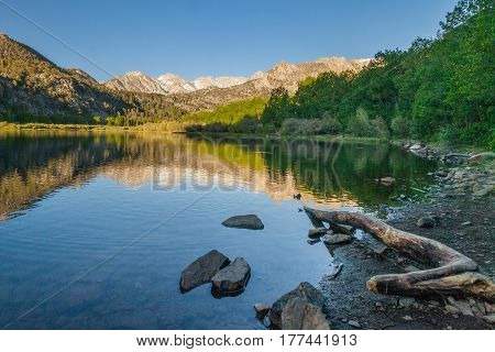 Morning reflection of the Sierra Nevada Mountains on an alpine lake in California.