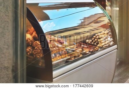 Rich variety of italian cookies donuts wafer in showcase of typical pastry shop in the street of Florence city at a sunny day with a sky reflection on display window