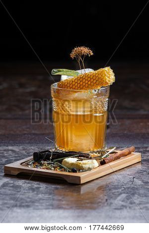 cold summer cocktail on a wooden dinette decorated with honeycomb and ice on a dark background