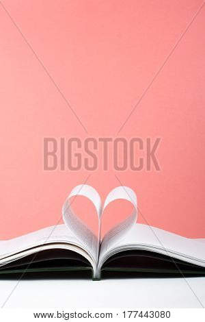 Old open hardback book page decorate into a heart shape for love in Valentine's. love with open book heart