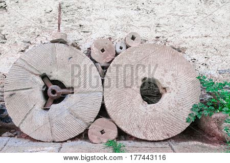Two millstones near the wall of a country house