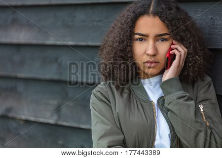 Outdoor portrait of beautiful sad aggressive mixed race African American girl teenager female young woman talking on red cell phone wearing green bomber jacket
