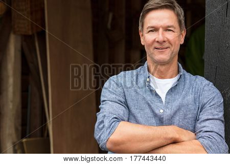 Portrait shot of an attractive, successful and happy middle aged man male arms folded outside wearing a blue shirt outside his garage or shed