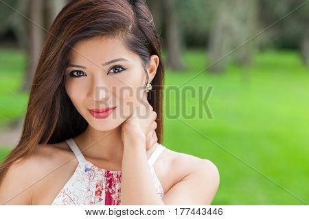Outdoor portrait of a beautiful young Chinese Asian young woman or girl in a natural green woodland setting