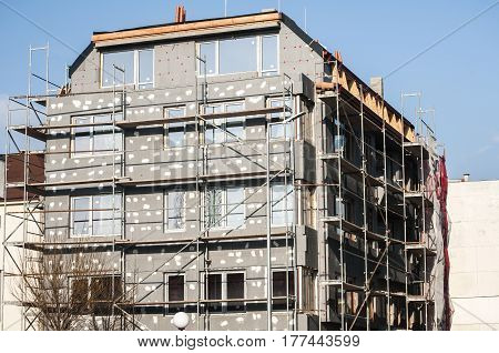 Building under construction with scaffolding for affixing the heat insulation