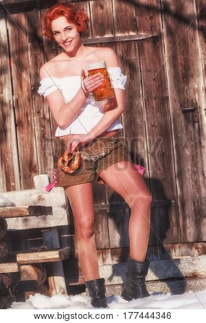 Bavarian young woman with beer and pretzel