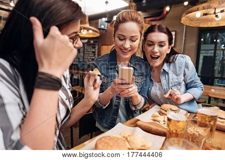 Food photography. Attractive females wearing jeans jackets taking photo of their dinner standing close to each other
