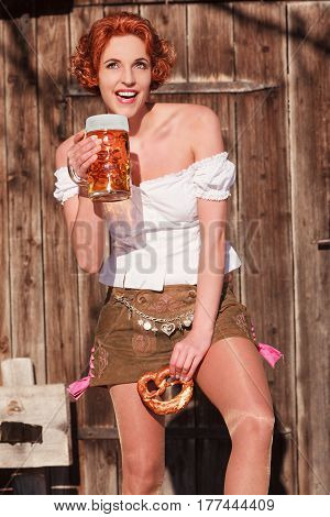 Redhead girl with beer and pretzel in shorts