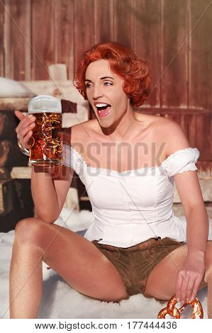 Laughing red-haired woman sitting in the snow with mug and pretzel