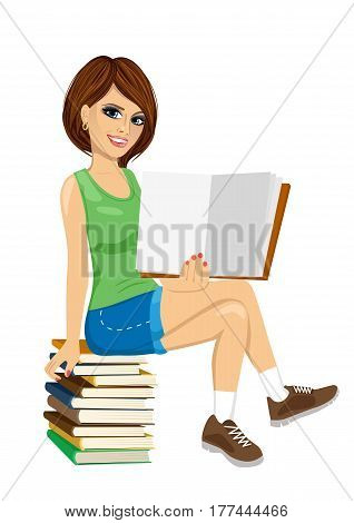 young student girl sitting on stack of books showing an open textbook