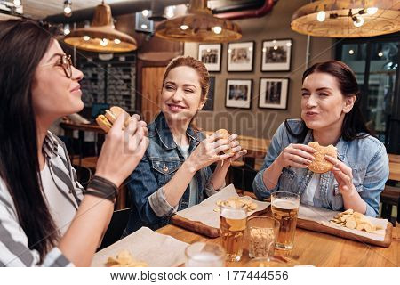 Delicious taste. Three young women holding burgers in hands squinting eyes while having dinner