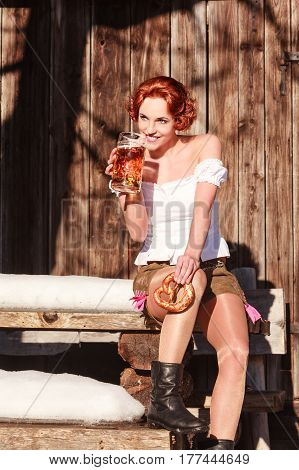 Young red-haired woman in leather pants with mug and pretzel sitting on a wooden bench