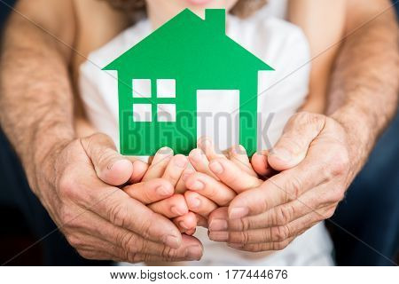 Family holding green eco house in hands. Moving and spring renovation concept