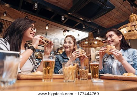 Enjoy your meal. Beautiful females holding burgers, having conversation during break