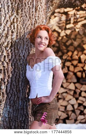 Portrait of a beautiful red-haired woman with cowl blouse and a shorts made from leather.