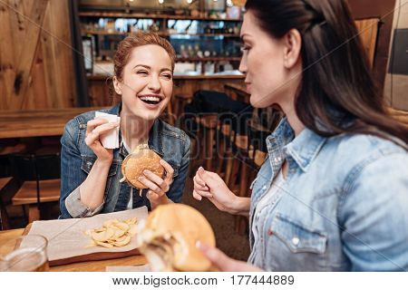 I am hungry. Two best friends wearing jeans shirts looking at each other while sitting in pub