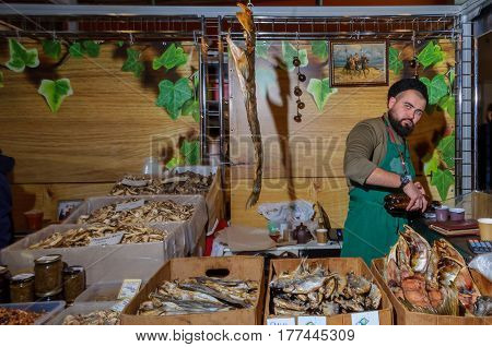 Moscow, Russia - February 25, 2017: Bearded seller of dried and smoked fish in a fur hat and apron at the time of the break at work on fair