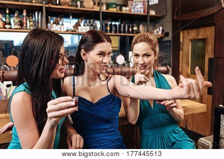 Come to me. Positive delighted bridesmaids wearing blue dresses keeping smile on faces while posing on camera