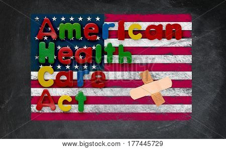 Childs magnetic letters spell American Health Care Act in congress. This is superimposed on a US flag chalked onto a blackboard with a bandage