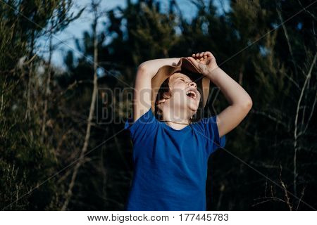 Raised hands up Smiling boy outdoor in summer forest. 6 years old kid in hat playing in nature.