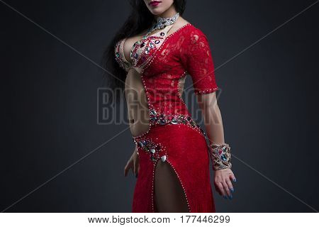 Young beautiful exotic eastern women performs belly dance in ethnic red dress on gray background studio shot
