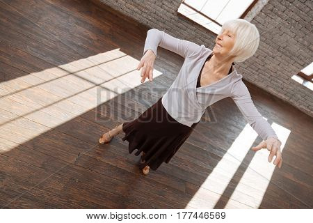 I do not care for my age. Happy capable aged woman performing in the ballroom while expressing joy and learning new dance step