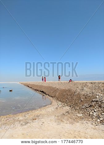 EIN BOCKES (DEAD SEA), ISRAEL - MARCH 08, 2017: Tourists walk on an artificial dam on the Dead Sea