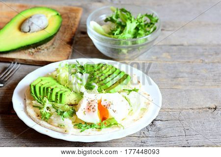 Healthy tortilla recipe. Tasty tortilla with a poached egg, avocado slices, napa cabbage, salad mix, sauce and spices on a plate and on vintage wooden background with copy space for text. Closeup