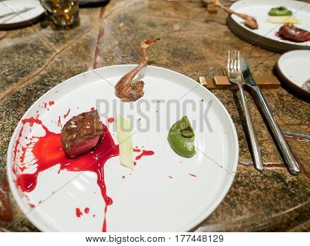 Royal pigeon steak with red currant sauce and grilled pigeon leg